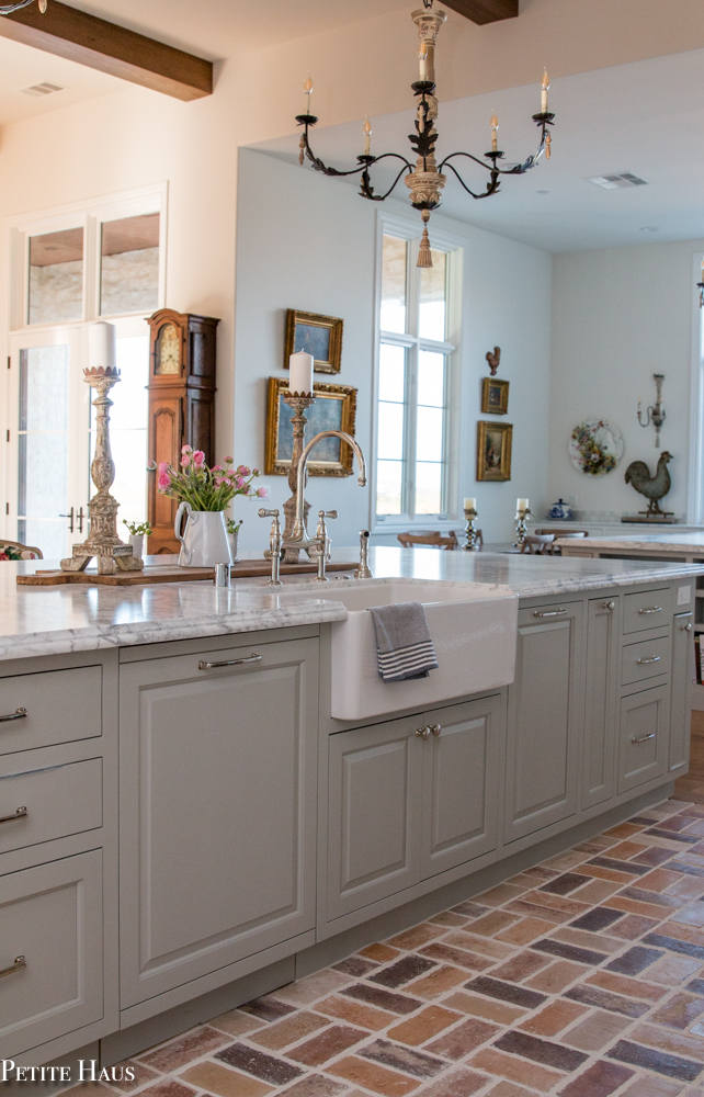 Gorgeous French country kitchen with huge kitchen island painted Benjamin Moore Silver Song, farm sink, and marble countertops. Design by Petite Haus.