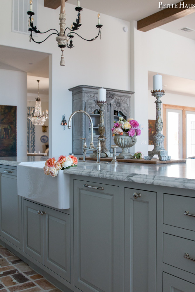 Lovely French country and French farmhouse style converge in a French kitchen by Petite Haus with island and farm sink. Island is  painted Benjamin Moore Silver Song.